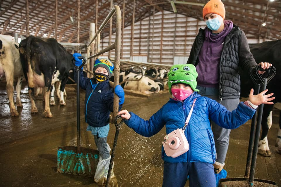two children and an adult standing in a cow barn with shovels