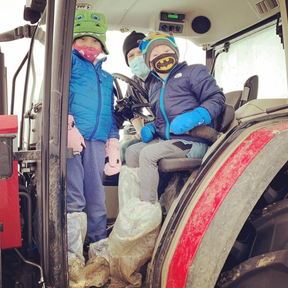 two children and a man in a tractor