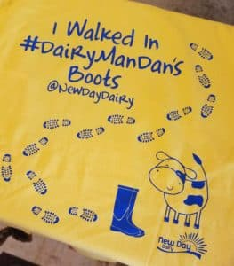 """back of a yellow t-shirt that says """"I walked in #DairymanDan's boots"""""""