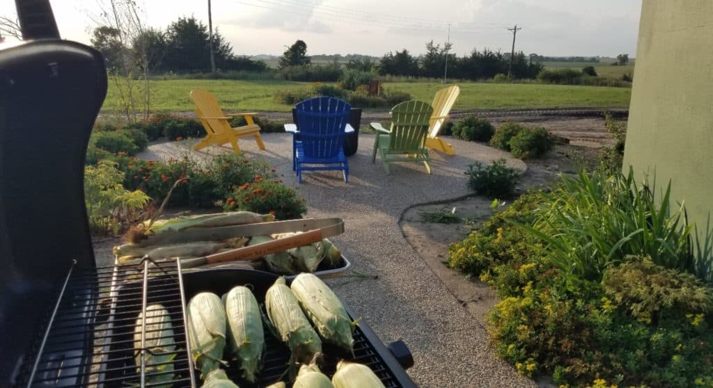 corn on a gas grill with patio beyond with colored patio chairs