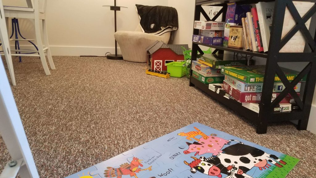 Puzzle on the floor with shelf full of games, DVD, and books behind it with a chair in the background