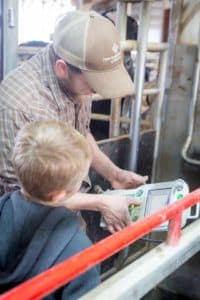 man and boy with robot milking controller