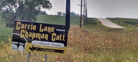 sign on country road pointing to Carrie Chapman Catt Girlhood Home