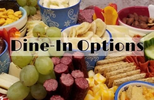 meat, cheese, crackers, fruit arranged on a chartcuterie borad