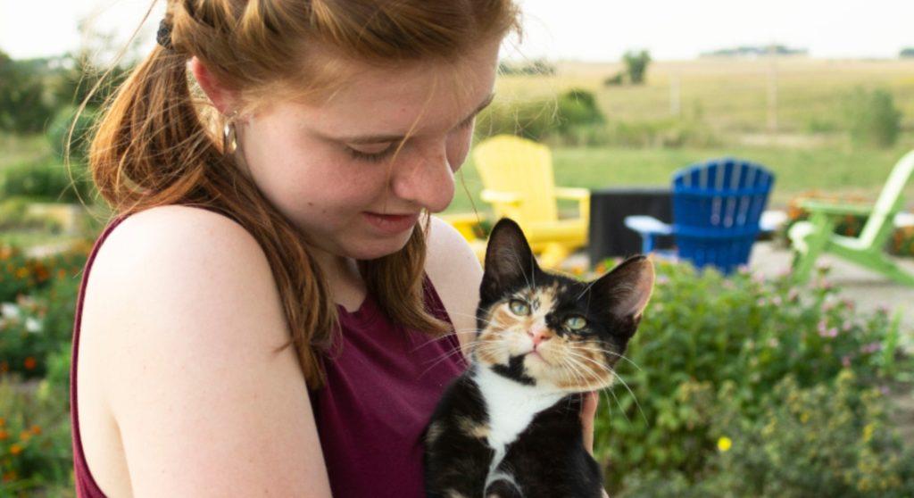 girl holding calico cat in garden