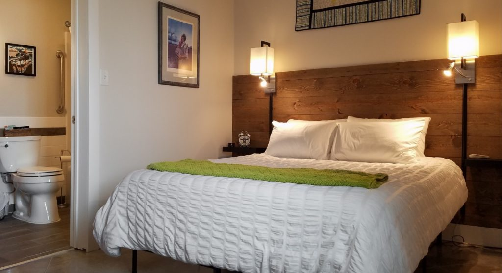 bed with white cover and lamps on wall beside it looking into bathroom with toilet