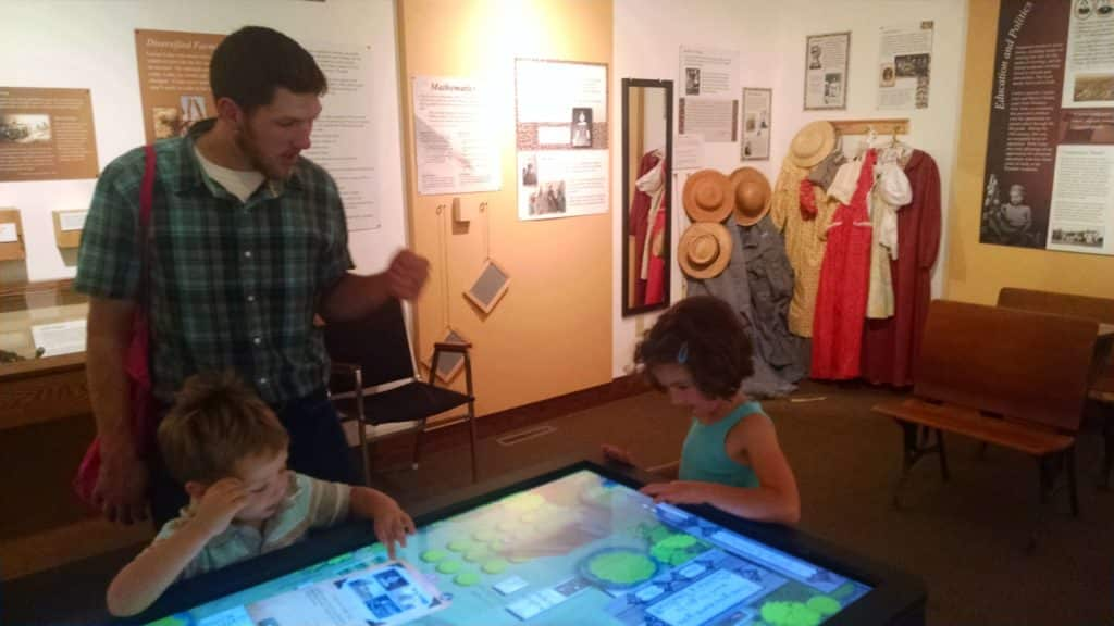 kids and dad in a museum playing a interactive touch screen table