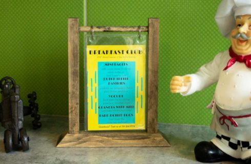 flip sign board with breakfast options with a statue of a chef on one side and metal tractor on the other