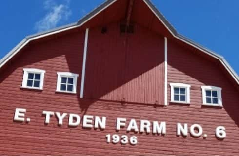 Close up view of large red barn with E Tyden Farm No. 6 1936 text in white