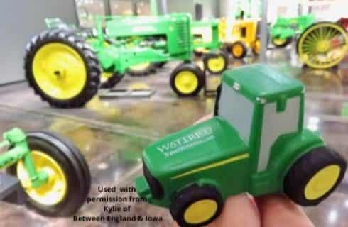 Regular sized old green and yellow tractors and a toy sized green and yellow tractor