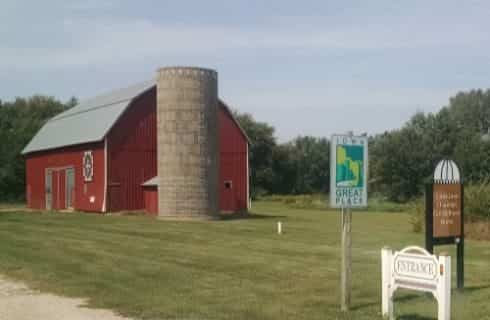 Large red barn with gray silo sitting in a field of green grass