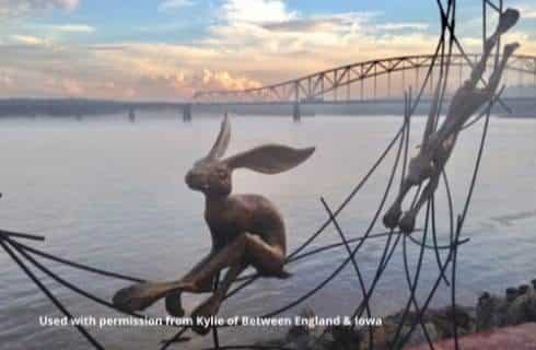 Metal sculpture of playful rabbits next to a body of water with a large bridge in the background