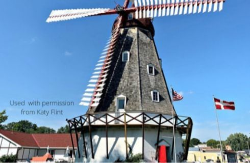Large windmill house with white painted walls and gray wood slats on top