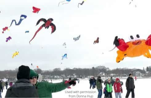 People with heavy coates flying multicolored kites in a field covered with snow