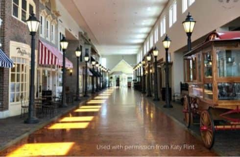 Long corridor of small store fronts and street lights inside a large building