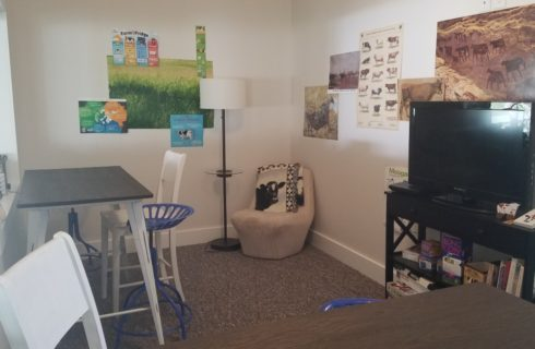 room with 2 pub tables, chair and console holding TV & games & puzzles