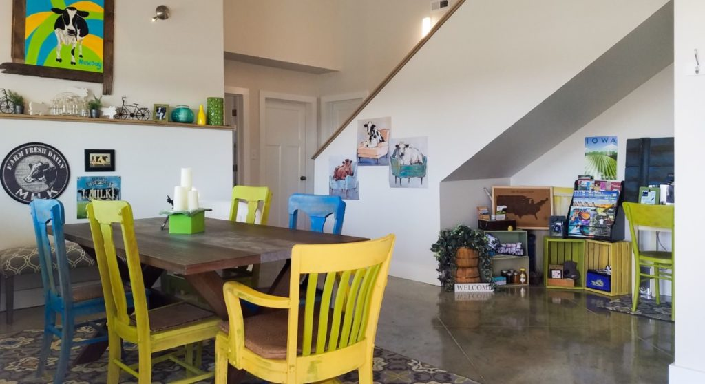 View of dining area with wooden table and blue and yellow chairs, a small nook with old crates storing items for sale, stairs leading upstairs, and cow artwork on the walls