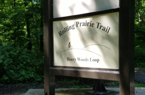 Large brown and cream steel sign for Rolling Prairie Trail surrounded by green trees