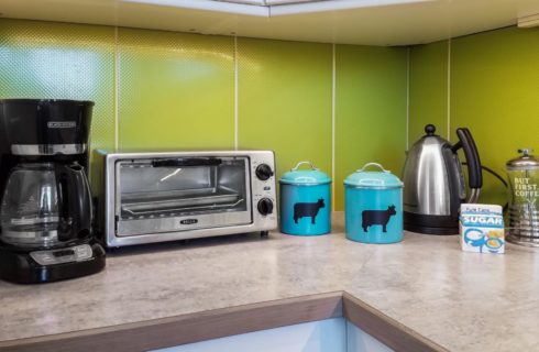 Close up view of a kitchen counter with green backsplash, coffee maker, toaster oven, teapot, and two turquoise containers with black dairy cows