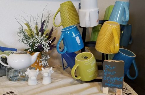 Close up view of a coffee cup stand with blue, green, yellow, and white cups, white cream dish, and white cow head salt and sugar shakers