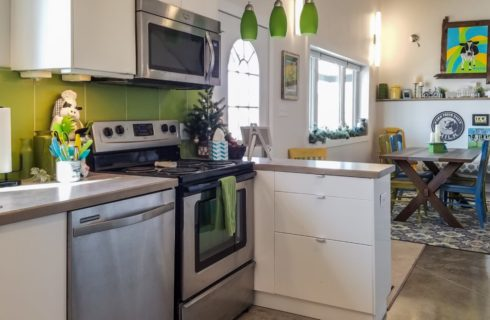 View of a kitchen with white cabinets, green backsplash, and stainless steel appliances and view into dining area with wooden table and green, yellow, and blue chairs