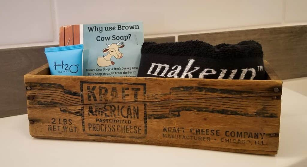 Close up view of old wooden crate filled with handmade soap, lotion, and black towel with the word makeup in white
