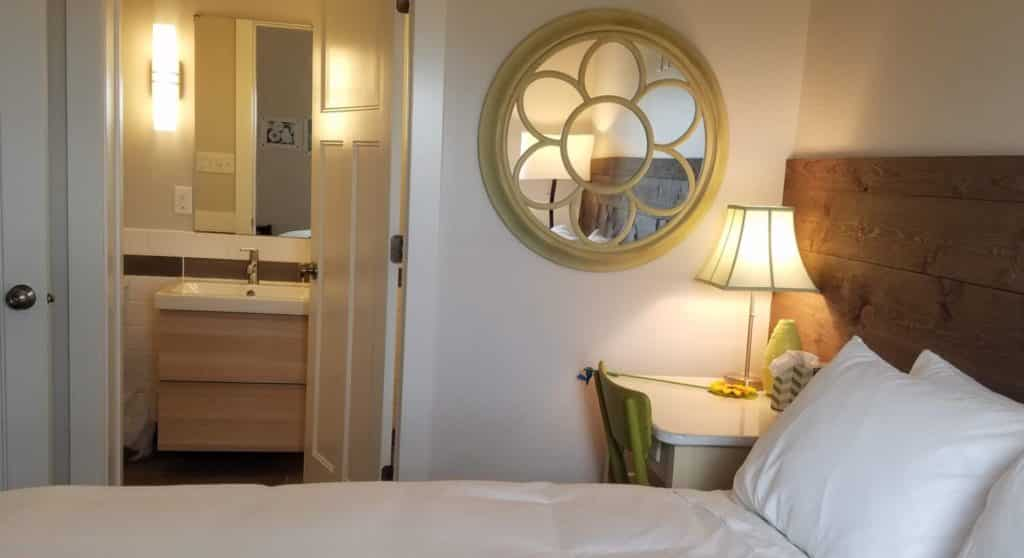 looking into attached bathroom with queen bed and bedside desk with lamp & mirror on wall