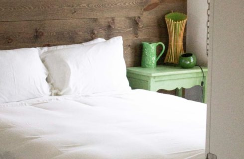 bed with white sheets with a green side table with green lamp