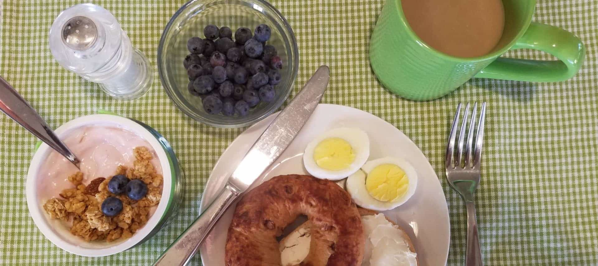 View from above looking down at a bagel with cream cheese, hard boiled egg cut in half, yogurt with granola and blueberries, bowl of blueberries, and green cup with coffee