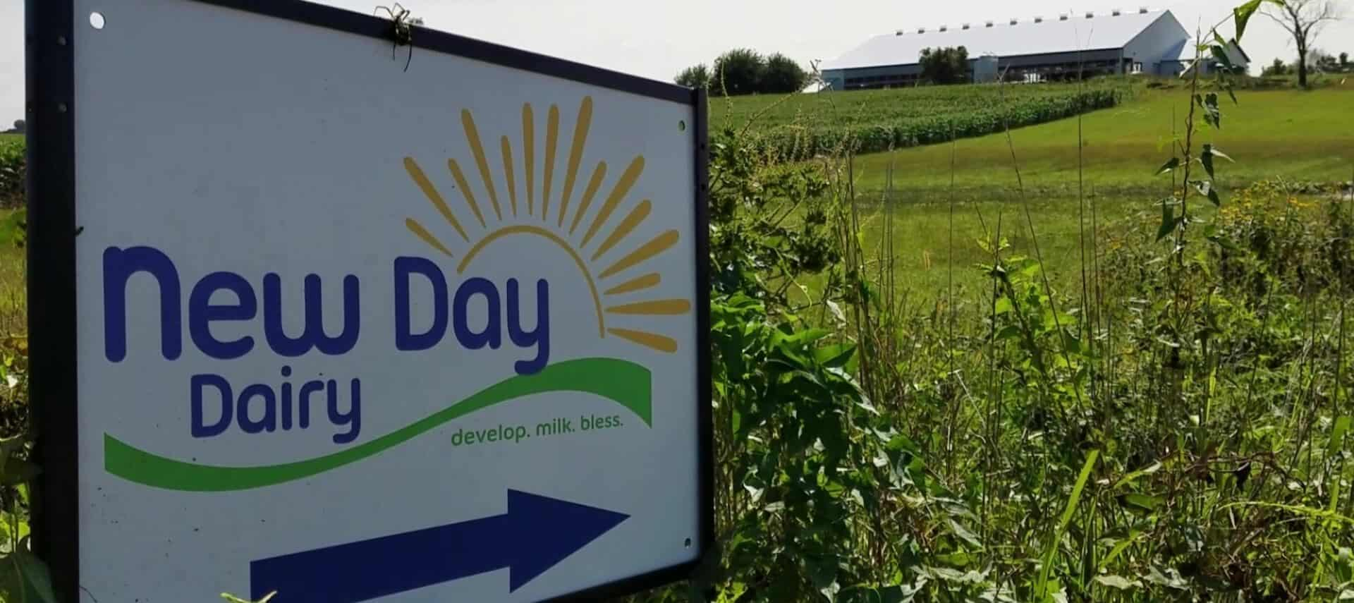 Large sign for New Day Dairy sitting in a large green field with the dairy barn in the background