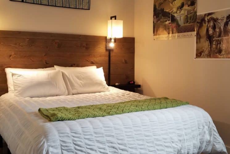 Bed with white bedding and green blanket, dark wooden slats on wall as accent and headboard, wall sconces, and artwork on the walls