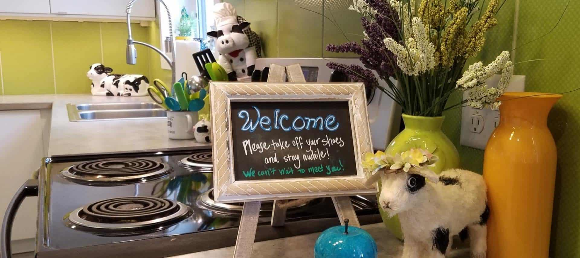 Close up view of countertop in a kitchen with a small Welcome sign, blue glass apple, orange and green vases, and stuffed black and white cow