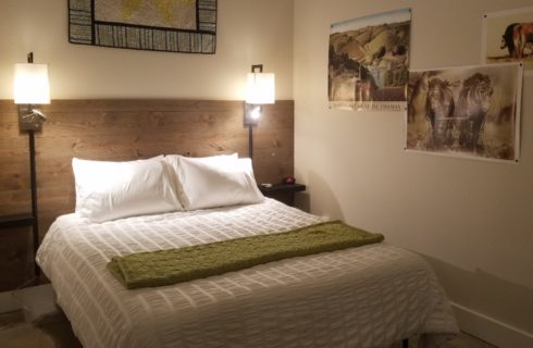 bed covered in white with lamps on wall beside, quilt above bed and posters on the wall of horses and countryside