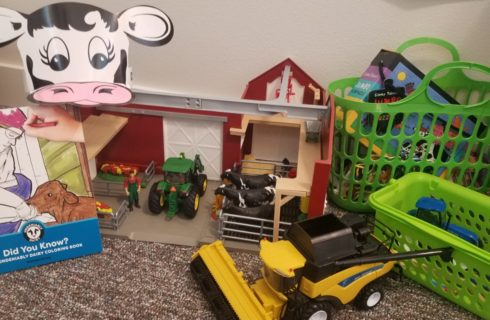toy barn with toy tractors, coloring book, and cow hat