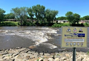 White Water Rapids at River with Sign