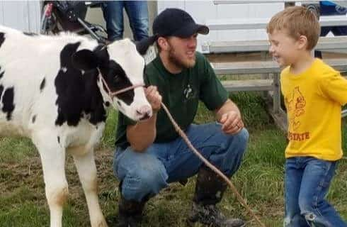 Man with green shirt holding a rope attached to a baby black and white calf for a kid with a yellow shirt