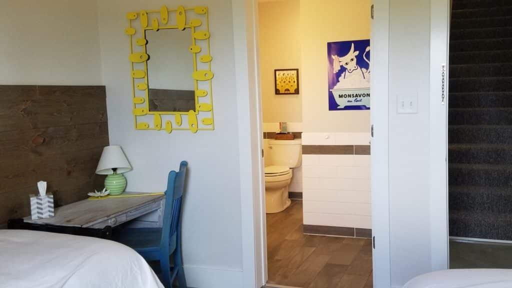 desk in bedroom next to door leading into a bathroom